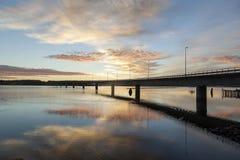 Brücke in reflektierendem Wasser mit einem großen Himmel Stockbild