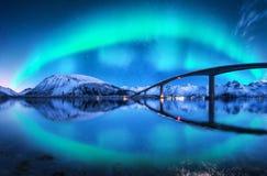 Brücke und aurora borealis über schneebedeckten Bergen stockfotos