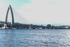 Brücken-Brücke über dem Seemodernen Brücke Zugang zu den Seesonniger Tagautos bereisen moderne Struktur der Seearchitektur lizenzfreie stockfotos