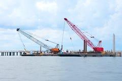 Brückenbau mit Raupenkränen auf den flachen Booten, die auf Wasser schwimmen Lizenzfreies Stockbild