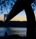 Brückenschattenbild über dem Schauen des Flusses Stockbilder