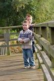 Brüder, die heraus über einem Teich im Herbst schauen Lizenzfreie Stockfotografie