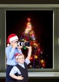Brüder fotografieren an der Kamera auf dem Hintergrund des Weihnachtsbaums außerhalb des Fensters Lizenzfreie Stockbilder