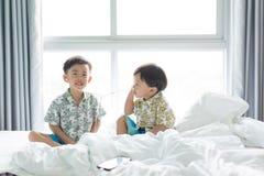 Brüder hören das Lied mit Handy morgens auf dem Bett stockfotografie