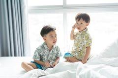 Brüder hören das Lied mit Handy morgens auf dem Bett stockbilder
