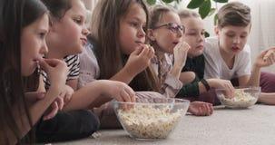 Br?der und aufpassender Film der Schwester und essen Popcorn stock footage