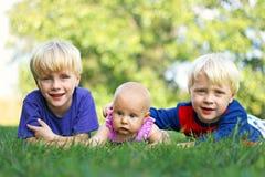 Brüder und kleine Schwesterchen, die sich draußen entspannen Lizenzfreie Stockfotografie