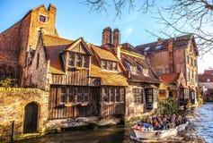 BRÜGGE, BELGIEN - 17. JANUAR 2016: Transportieren Sie Boot mit Touristen, die auf altem Gebäude der mittelalterlichen Stadt schau Stockfotografie