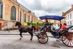 BRÜGGE, BELGIEN - 10. JUNI 2014: Pferdewagen auf Straße von Brügge, Belgien Stockfotografie