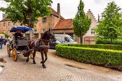 BRÜGGE, BELGIEN - 10. JUNI 2014: Pferdewagen auf Straße von Brügge, Belgien Lizenzfreie Stockfotografie