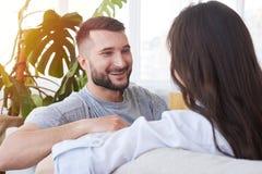 Brünette und bärtiger Mann, die beim Haben des Restes auf Sofa plaudern Lizenzfreies Stockfoto