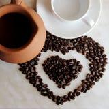 brąz gliniana turczynka dla kulinarnej kawy, biały spodeczek, filiżanka i piec kawowe fasole w formie serca na stole, obrazy stock