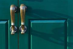 Brąz rękojeści ciskają cienie na zielonym drzwi Obraz Royalty Free