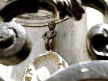 Brązowa rzeźba Manneken Pis jako widok Przez Żelaznego ogrodzenia, Mały ale Sławny punkt zwrotny Bruksela obrazy stock