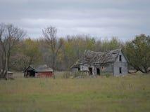 Brązowawy Zaniechany Obdrapany gospodarstwo rolne dom, jata z chmurami i fotografia stock