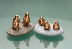 Brązowe figurki pięć pingwinów stoi na okrzesanych kamieniach Zdjęcie Stock