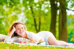 Brązowooka dziewczyna z jabłkami i książką Zdjęcie Royalty Free