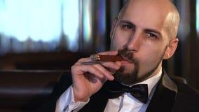 Brązowooki łysy mężczyzna Dymi cygaro i patrzeje kamerę, zwolnione tempo zdjęcie wideo