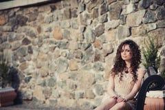 Brązowooki brunetki dziewczyny obsiadanie na ławce obrazy stock