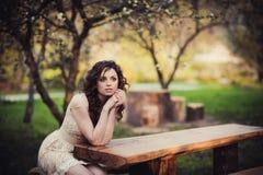 Brązowooki brunetki dziewczyny obsiadanie na ławce fotografia stock