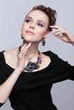 Brązowowłosa młoda kobieta z bijouterie na szarym tle obraz stock