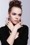 Brązowowłosa młoda kobieta z bijouterie na szarym tle fotografia stock