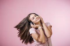 Brązowowłosa rozochocona dziewczyna słucha muzyka na różowym tle z hełmofonami zdjęcia royalty free