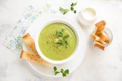 Br?culi de la sopa de verduras, guisantes, calabac?n, espinaca poner crema verdes) con la tostada, cuscurrones Primavera sana veg imagenes de archivo