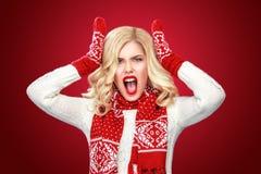 Bär iklädd jul för ilsken blond kvinna waitnggåvor som isoleras på röd bakgrund Royaltyfria Bilder