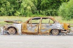 Brûlé en bas de l'épave de voiture du côté de la route Photographie stock