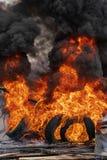 Br?nnande bilgummihjul, stark flamma av r?d brand och moln av svarta dunster i himmel arkivfoton
