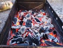 Br?nnande kol och vedtr? p? gallerspisgallret F?rberedelse av kol f?r grillfest i det ?ppna gallret Begreppet av arkivfoto