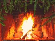Br?nnande vedtr? i en spis som dekoreras f?r jul med filialer av granen royaltyfri foto