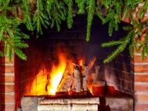 Br?nnande vedtr? i en spis som dekoreras f?r jul med filialer av granen royaltyfri fotografi