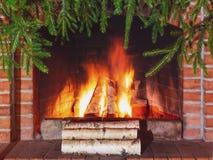 Br?nnande vedtr? i en spis som dekoreras f?r jul med filialer av granen arkivfoton