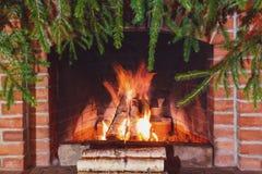 Br?nnande vedtr? i en spis som dekoreras f?r jul med filialer av granen arkivfoto
