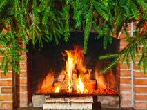Br?nnande vedtr? i en spis som dekoreras f?r jul med filialer av granen arkivbild