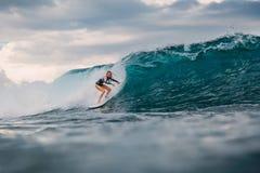 Br?nningflicka p? surfingbr?dan Surfarekvinna och blå våg royaltyfri foto