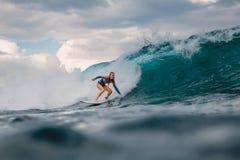 Br?nningflicka p? surfingbr?dan Surfarekvinna och blå våg royaltyfria bilder
