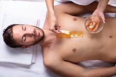 Br?stkorg f?r ` s f?r kosmetologApplying Wax On man royaltyfri fotografi
