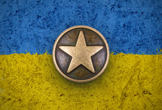 Brązowa gwiazda na Ukraina flaga tle Fotografia Royalty Free
