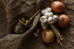 Brązowy morter i grupa garlics i cebule Obrazy Stock