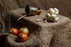Brązowy morter i grupa garlics i cebule Fotografia Stock