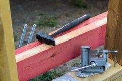 braçadeira do parafuso do martelo e da mão no fundo da construção imagens de stock