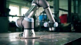 Braço automatizado que move sobre uma tabela, trabalhando em uma planta filme