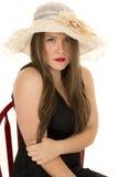 Braço de mão vermelho do chapéu da cadeira do vestido do preto da mulher sério Imagem de Stock
