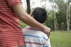 Braço de And Son Standing do pai ao redor no parque Fotografia de Stock