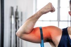 Braço destacado do bíceps de medição do homem com fita de medição imagem de stock royalty free