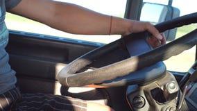 Braço do camionista no leme como conduz Mão masculina que guarda o volante grande quando caminhão das movimentações Camionista pa filme