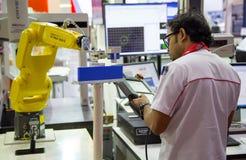 Braço do robô do controle do trabalhador a carregar e a descarregar o workpiece imagem de stock royalty free